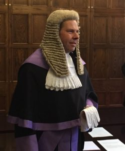 Male judge in judicial robe and wig